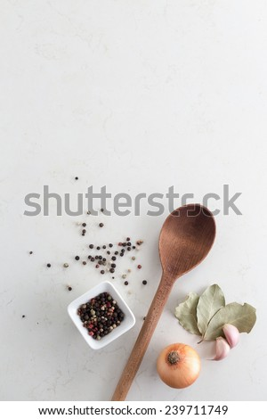 Wooden spoon with bay leaves, garlic bulbs and small bowl of pepper corns - stock photo