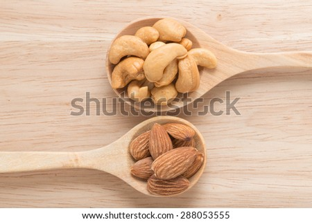 Wooden spoon with cashew nuts and almonds - stock photo