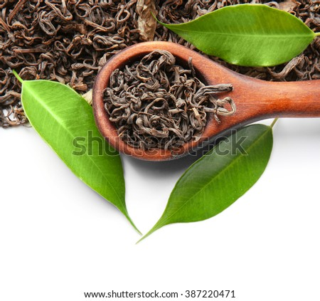 Wooden spoon with dry tea and green leaves, isolated on white