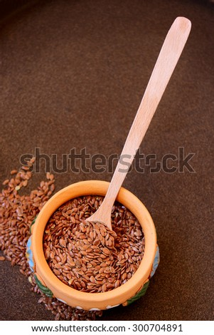 Wooden spoon with flax seeds in a bowl placed on a metal background, selective focus - stock photo