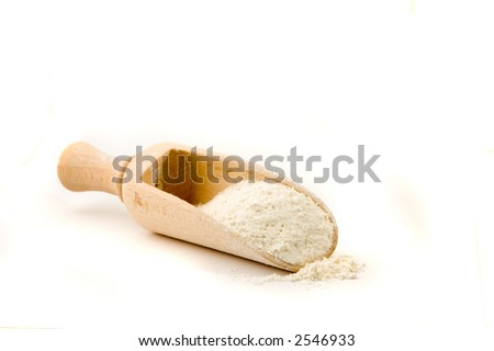 Wooden spoon with flour in it - stock photo