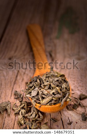 Wooden spoon with green tea - stock photo
