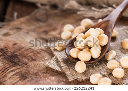 Wooden spoon with Macadamia nuts (detailed close-up shot) - stock photo
