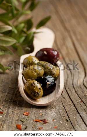 Wooden spoon with mix of olives on old wooden table - stock photo
