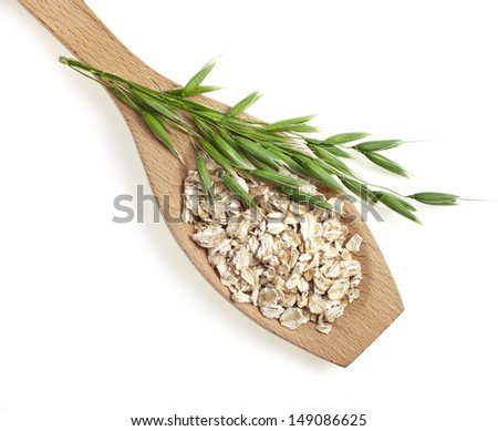 wooden spoon with oat seeds close up  top view surface isolated on white background - stock photo