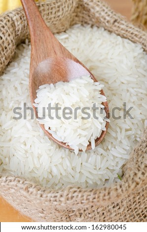 wooden spoon with raw rice in gunny bag.  - stock photo