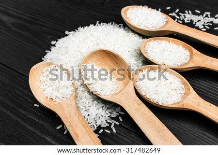 wooden spoon with raw rice on the black table - stock photo