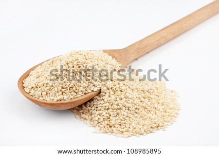 Wooden spoon with sesame seeds on a white background