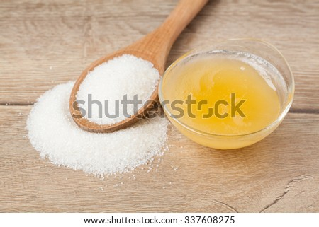 Wooden spoon with sugar and bowl with honey - stock photo