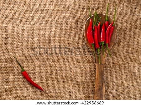 Wooden spoon with Thai spicy chili pepper on burlap canvas