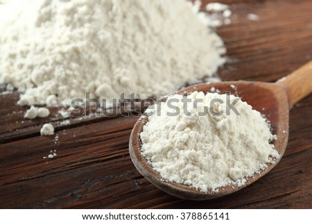 Wooden spoon with wheat flour on plank table