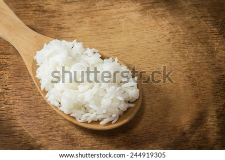 wooden spoon with white boiled rice on wood background