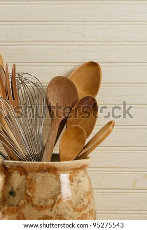 Wooden spoons and wire whisks in an old yellow and brown pot against a weathered wood background.