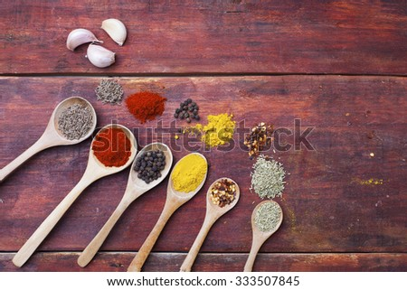 Wooden spoons full of aromatic herbs and spices on a rustic wooden cutting board