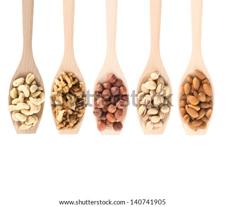 Wooden spoons full of different kinds of nuts: peanut, hazelnut, walnut, almond, pistachio, isolated over white background, top view - stock photo
