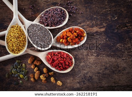 Wooden spoons of various superfoods on old wooden background - stock photo