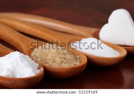 Wooden spoons with different kinds of sugar