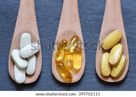 Wooden spoons with healthy supplements on a dark stone background