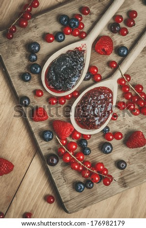 Wooden spoons with jams an berries on the wooden table - stock photo