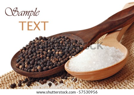 Wooden spoons with sea salt and peppercorns on white background with copy space. Macro with shallow dof. - stock photo