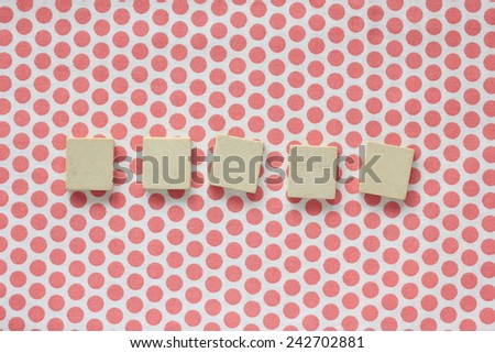 wooden squares on polka-dotted fabric - stock photo