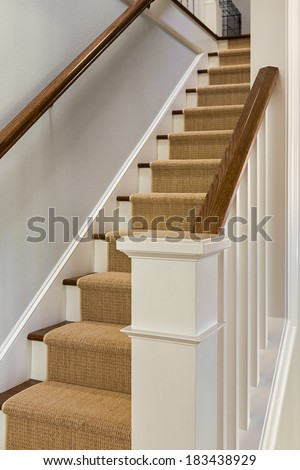Wooden staircase and banister  with carpet runner and white molding.  - stock photo