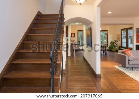 Wooden Staircase in Mediterranean Villa with adjacent living room. - stock photo