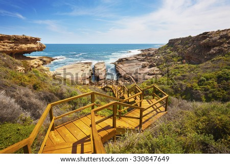 Wooden staircase leading down to a rugged, untouched coastline. - stock photo