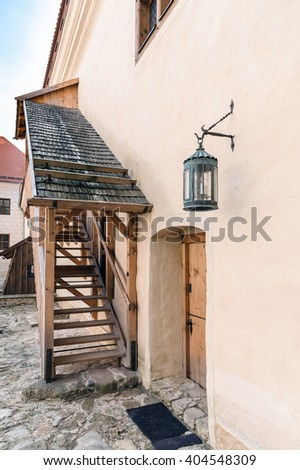 Wooden stairs and lamp near wall of Bauska castle, Latvia - stock photo