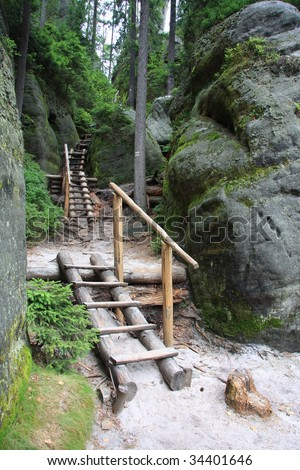 Wooden stairs climbing between rocks an trees