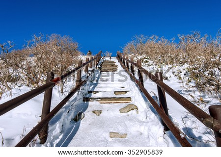 Wooden stairs on a hillside in winter. Deogyusan mountains in South Korea. - stock photo