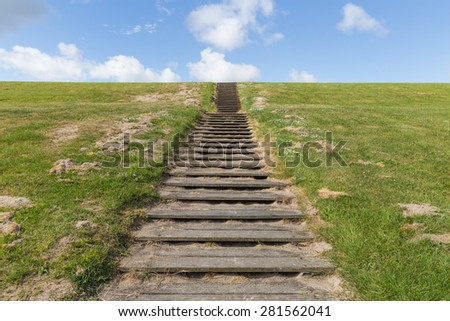 Wooden stairs upon green hill with a blue sky - stock photo