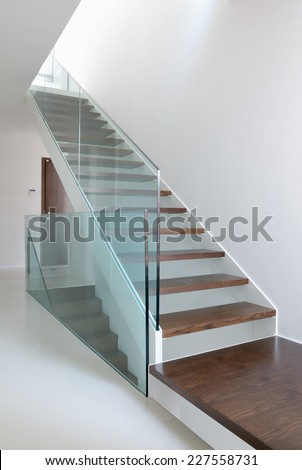 wooden stairs with glass balustrade in modern interior and white epoxy flooring - stock photo