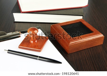 Wooden stamp with clipboard and books on table - stock photo