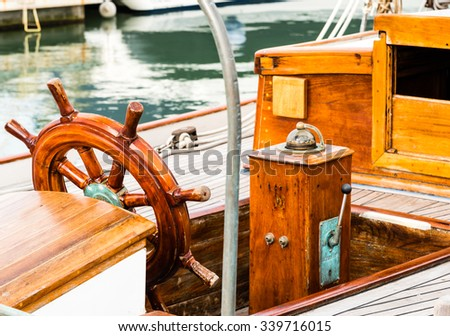 wooden steering wheel and compass on a vintage sailing boat - stock photo