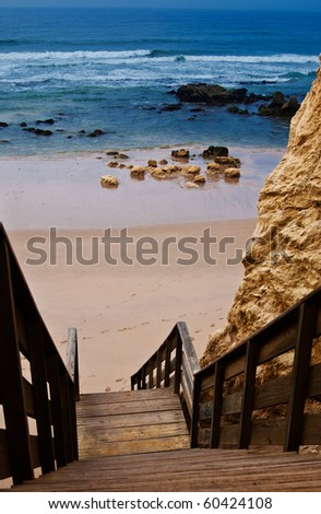 Wooden steps to Praia da Rocha an the Atlantic Ocean in Algarve, southern Portugal. - stock photo