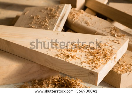 Wooden sticks lie on a workbench in the carpentry workshop - stock photo