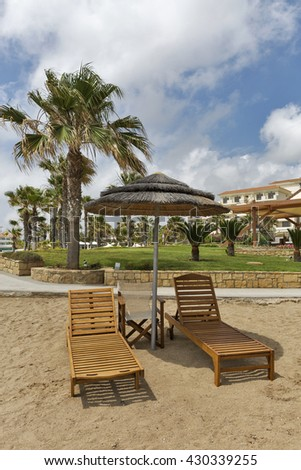 Wooden sunbeds and straw umbrella for relaxation on the Mediterranean sea sand beach in Paphos, Cyprus. - stock photo
