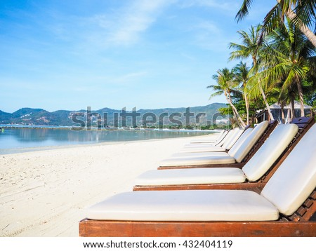 Wooden sunbeds on the nice sand beach with sea and coconut tree background