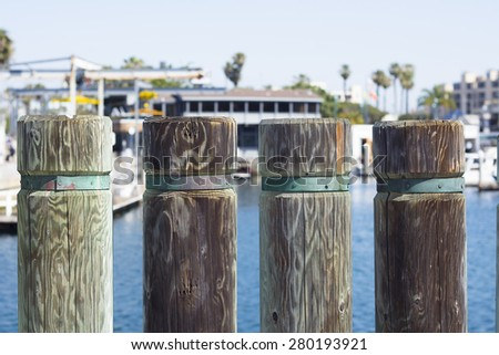 Wooden support posts on a shoreline boardwalk in Redondo Beach California during a bright, sunny day - stock photo