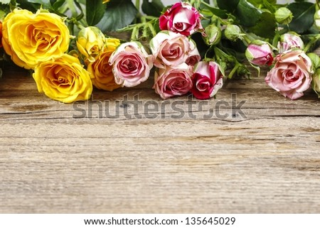 Wooden surface with copy space decorated with colorful roses. - stock photo