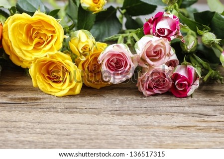Wooden surface with copy space decorated with colorful roses - stock photo