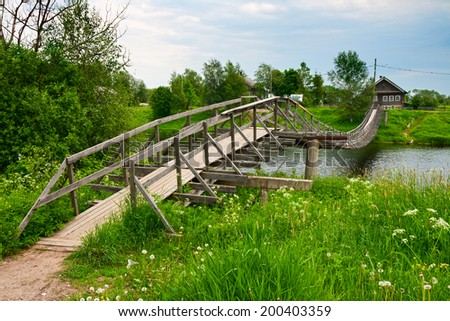 Wooden suspension bridge across the river in a Russian village - stock photo