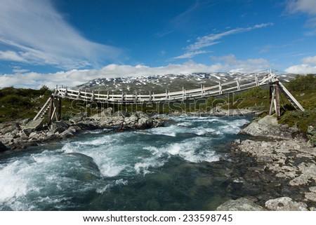 Wooden suspension footbridge over the mountain river, Norway - stock photo