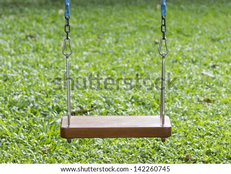 Wooden swing and green grass background - stock photo