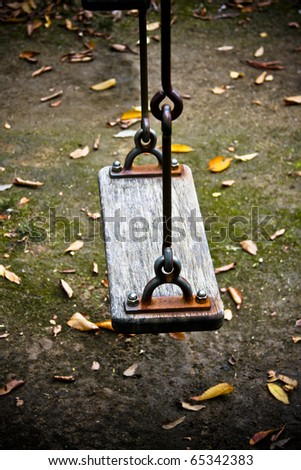 Wooden swing chair in autumn park - stock photo