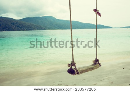 Wooden swing on beautiful white sand tropical beach, Thailand. retro filter. - stock photo