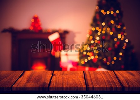 Wooden table against christmas tree with presents near the fireplace - stock photo