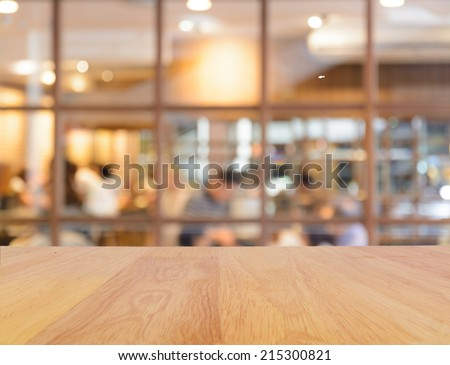 Wooden table and blur restaurant background - stock photo
