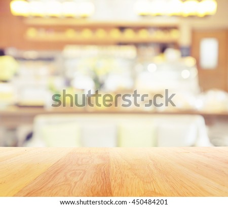 Wooden table and blur restaurant coffee shop background